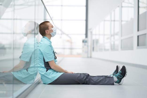 Koncepcja wypalenia zawodowego. wyczerpana kaukaska kobieta krótka fryzura lekarz, ubrana w maskę medyczną, siedząca na podłodze w korytarzu kliniki z zamkniętymi oczami