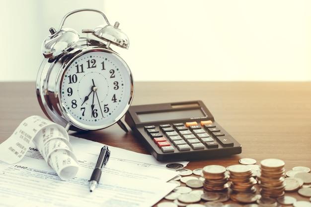 Koncepcja wypełniania podatków. formularz podatkowy 1040 z długopisem, zegarem, monetami i kalkulatorem na biurku. koncepcja podatkowa