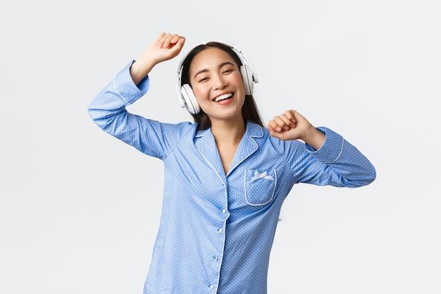 Koncepcja wypoczynku w domu, weekendy i styl życia. wesoła szczęśliwa azjatycka dziewczyna w piżamie bawi się, tańczy do muzyki w słuchawkach, słucha ulubionej piosenki w dzień wolny, stoi radosne białe tło