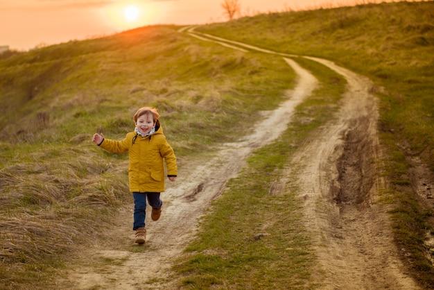 Koncepcja wypoczynku z dzieciństwa i ludzi - szczęśliwy mały chłopiec biegający na jesiennym polu parku