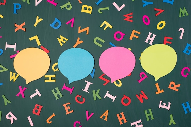 Koncepcja wyrażania opinii. widok z góry na zdjęcie czterech kolorowych bąbelków myśli na zielonej tablicy z wielokolorowymi literami
