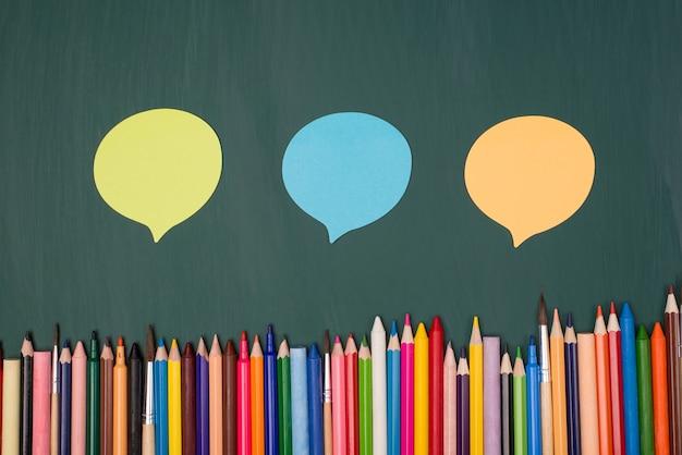Koncepcja wyrażania opinii. widok z góry na zdjęcie trzech kolorowych baniek myśli na zielonej tablicy za pomocą wielokolorowych ołówków