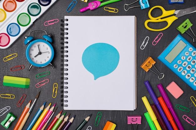 Koncepcja wyrażania opinii. zdjęcie z góry nad głową, przedstawiające kolorowe długopisy i ołówki wokół pustego notatnika z niebieską naklejką bąbelkową na białym tle na tablicy