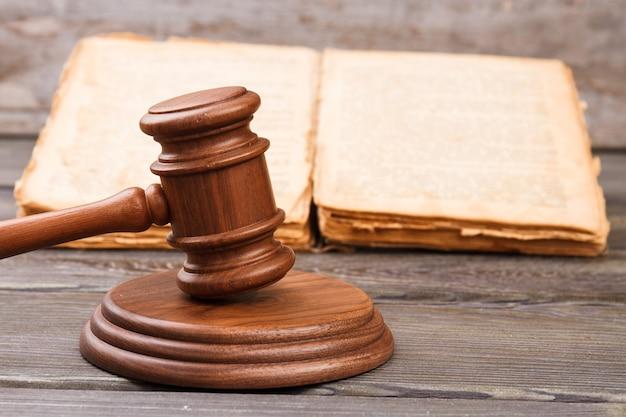 Koncepcja wyroku sądowego. drewniany młotek uderza w brzmiący blok. otwarta stara, zużyta książka.