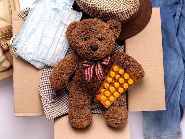 Koncepcja wysyłania opieki, darowizn. w pudełku witaminy, rzeczy, maseczki i pluszowy miś