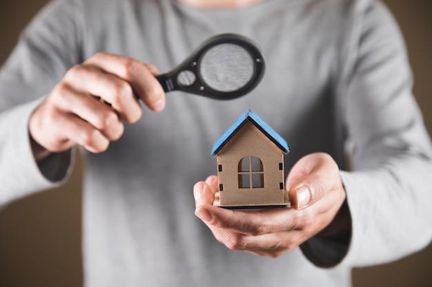 Koncepcja wyszukiwania w domu. mężczyzna trzymający lupę i dom