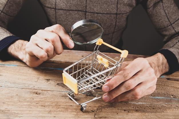 Koncepcja wyszukiwania zakupów. szkło powiększające patrząc na kosz