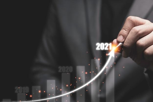 Koncepcja wzrostu gospodarczego i inwestycyjnego 2021, biznesmen pisze strzałkę trendu wzrostu z wykresem słupkowym.