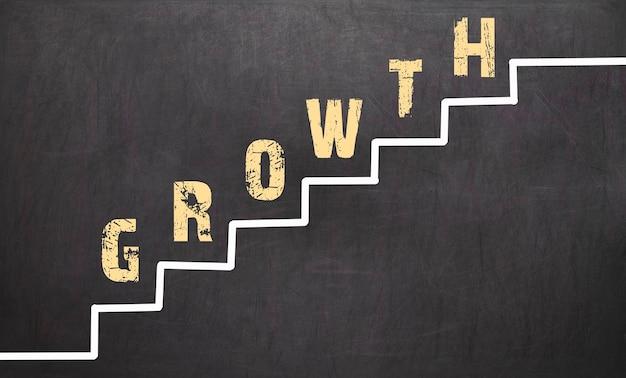 Koncepcja wzrostu na czarnej tablicy ręką biznesmena