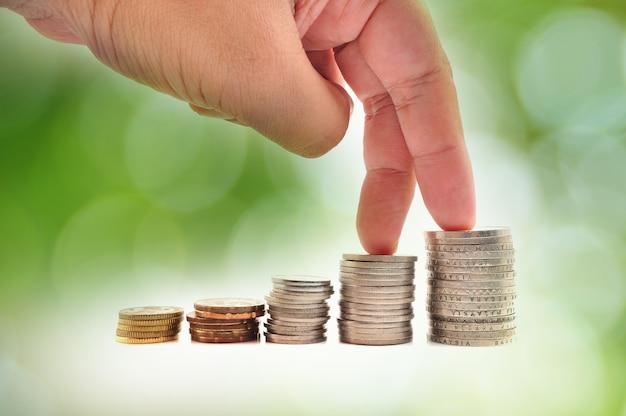Koncepcja wzrostu. palce chodzące po stosach monet na białym tle