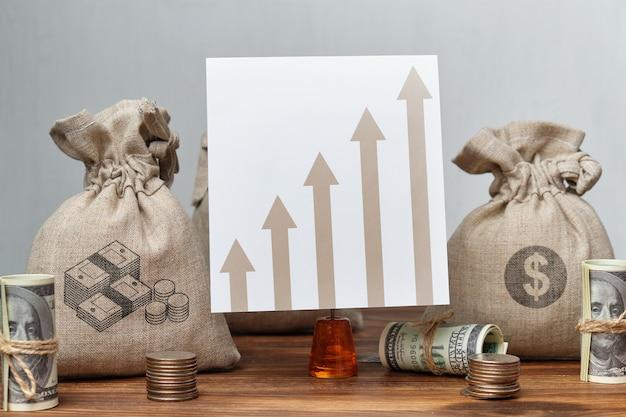 Koncepcja wzrostu zysku na wykresie ze strzałkami i workami pieniędzy