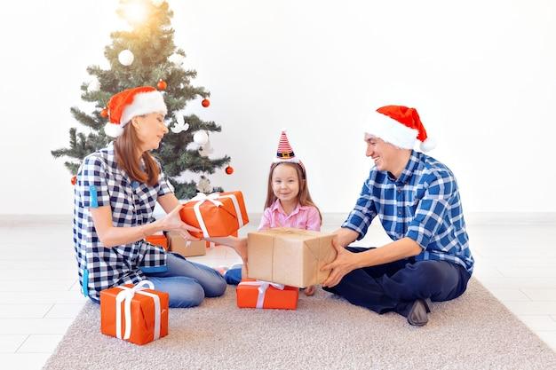 Koncepcja x-mas i wakacje - rodzina otwierająca świąteczny prezent przed drzewem.