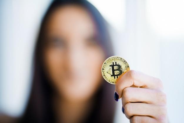 Koncepcja z bliska. skoncentruj się na złotym bitcoinie jako głównej krypto-walucie, posiadającej ładną modelkę