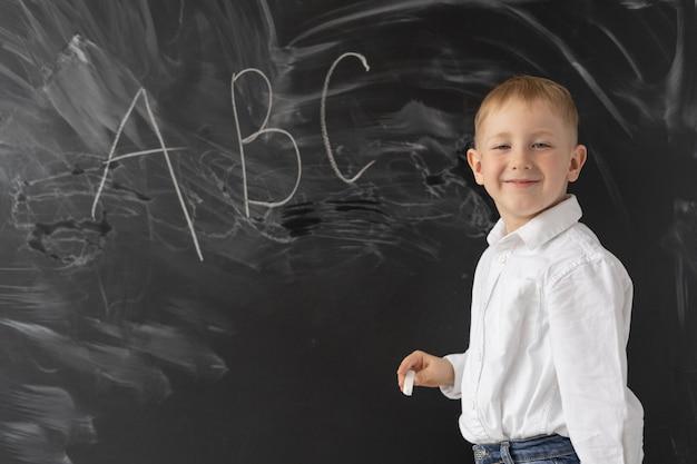 Koncepcja z powrotem do szkoły. obok tablicy szkolnej stoi mały chłopiec