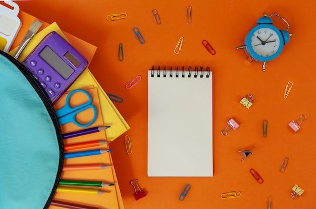 Koncepcja z powrotem do szkoły. turkusowy plecak szkolny z materiałami na pomarańczowo