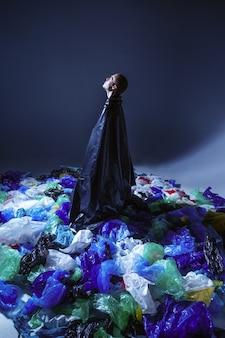 Koncepcja z problemami ekologicznymi, dowody zanieczyszczenia, odizolowana na ciemnej ścianie pracowni. młody człowiek w studio, otoczony pustymi plastikowymi workami na śmieci.