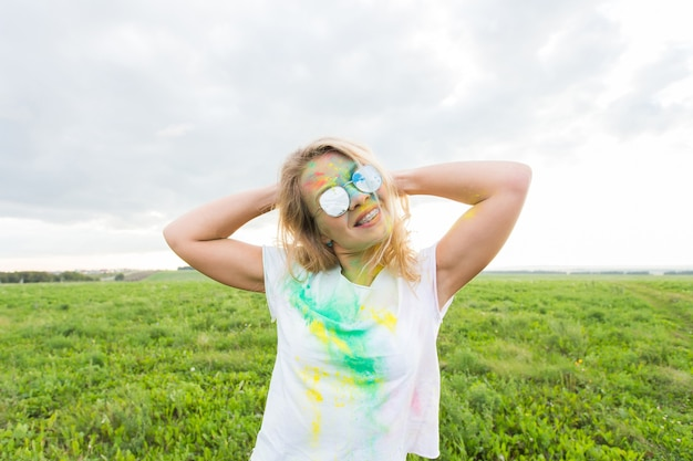 Koncepcja zabawy, festiwalu holi i wakacji - śmieszna kobieta pokryta kolorowym proszkiem uśmiechnięty