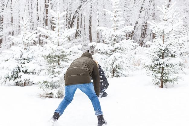 Koncepcja zabawy, sezonu i wypoczynku - para miłości gra zima drewno na śniegu.