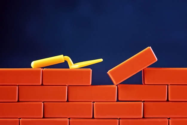 Koncepcja zadania końcowego. brickwork i budynek kielnia na ciemnym tle