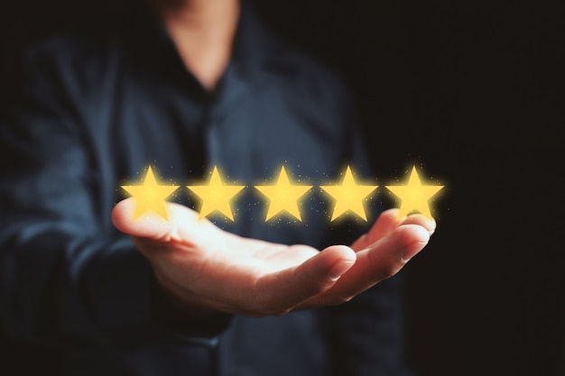 Koncepcja zadowolenia klienta. dłoń trzymająca gwiazdki, aby ukończyć pięć gwiazdek.