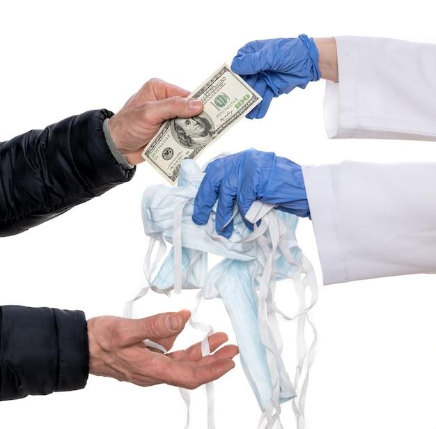 Koncepcja zakażenia koronawirusem covid-19. lekarz w niebieskich rękawiczkach sprzedający niebieskie maski medyczne za 100 dolarów mężczyźnie na białym tle