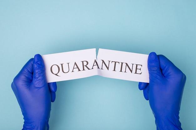 Koncepcja zakończenia kwarantanny. widok z góry na zdjęcie rąk w rękawiczkach rozdzierających słowo kwarantanny na białym tle na niebieskim tle