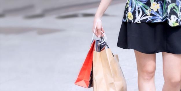 Koncepcja zakupów; biznesowej kobiety ręka trzyma torba na zakupy w jeden ręce przy zakupy centrum handlowym po ciężkiej pracy
