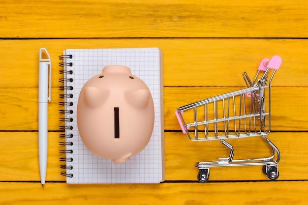 Koncepcja zakupów, gospodarka, lista zakupów. skarbonka z wózkiem supermarketu, notatnik na żółtej powierzchni drewnianej. widok z góry