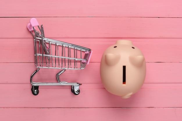 Koncepcja zakupów, gospodarka. skarbonka z wózkiem supermarketu na różowej powierzchni drewnianej. widok z góry