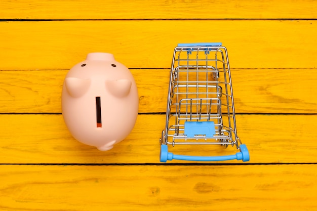 Koncepcja zakupów, gospodarka. skarbonka z wózkiem supermarketu na żółtej drewnianej powierzchni. widok z góry