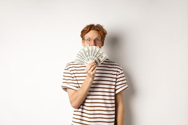 Koncepcja zakupów i finansów. szczęśliwy rudy facet wygrywając, pokazując nagrodę pieniężną i uśmiechając się szczęśliwy do kamery, stojąc w okularach i t-shirt na białym tle.