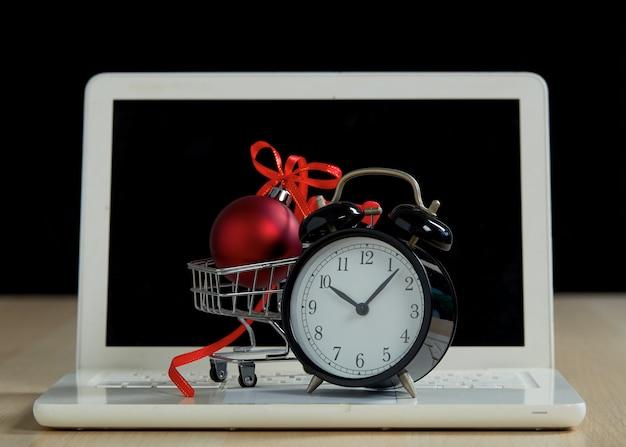 Koncepcja zakupów i sprzedaży detalicznej w czarny piątek. wózek na zakupy wózek laptop i czerwona bombka z kokardą na drewnianym stole z czarnym tłem. koncepcja marketingu lub zakupu supermarketu online.