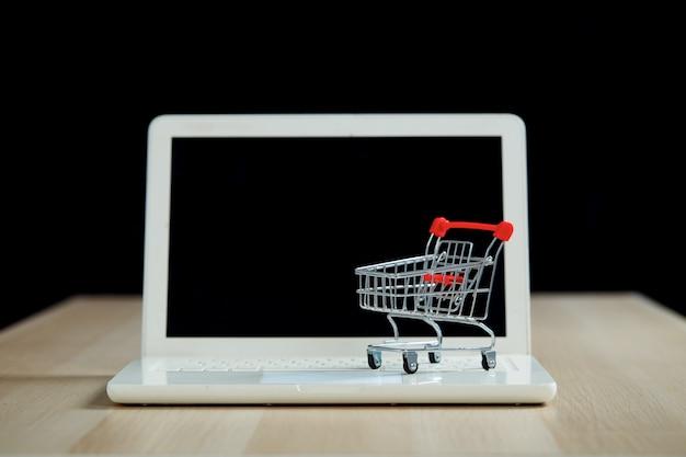 Koncepcja zakupów i sprzedaży detalicznej w czarny piątek. wózek na zakupy wózek laptop na drewnianym stole z czarnym tłem. koncepcja marketingu lub zakupu supermarketu online.