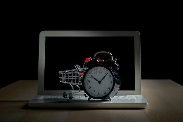 Koncepcja zakupów i sprzedaży detalicznej w czarny piątek. wózek na zakupy wózek laptop z zegarem na drewnianym stole z czarnym tłem. koncepcja marketingu lub zakupu supermarketu online.