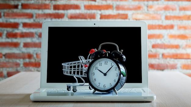 Koncepcja zakupów i sprzedaży detalicznej w czarny piątek. wózek na zakupy wózek laptop z zegarem na drewnianym stole z czerwoną ceglaną ścianą. koncepcja marketingu lub zakupu supermarketu online.