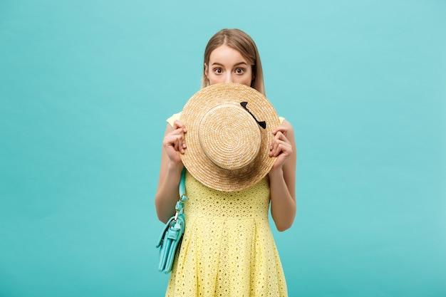 Koncepcja zakupów i sprzedaży: piękna nieszczęśliwa młoda kobieta w żółtej eleganckiej sukni z torbą na zakupy.