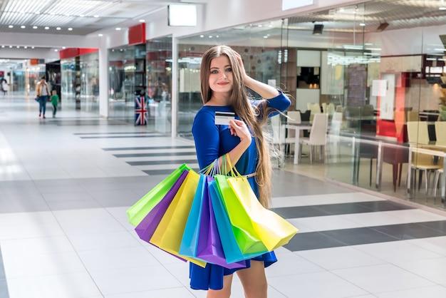 Koncepcja zakupów, kobieta z kartą kredytową i torbami