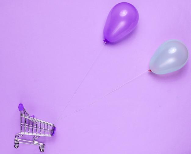 Koncepcja zakupów mini wózek na zakupy, balony niebieskie i różowe