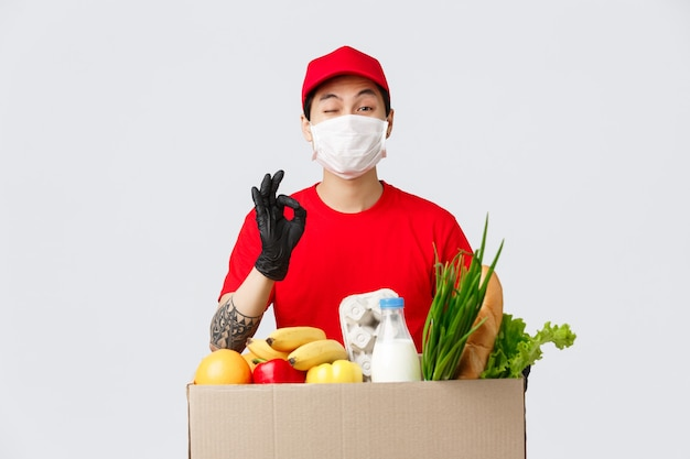 Koncepcja zakupów online, dostawy żywności i pandemii koronawirusa. uśmiechnięty azjatycki kurier w mundurze pokazuje znak porządku, przekazuje klientowi jego zamówienie, świeże artykuły spożywcze ze sklepu internetowego, nosi maskę medyczną