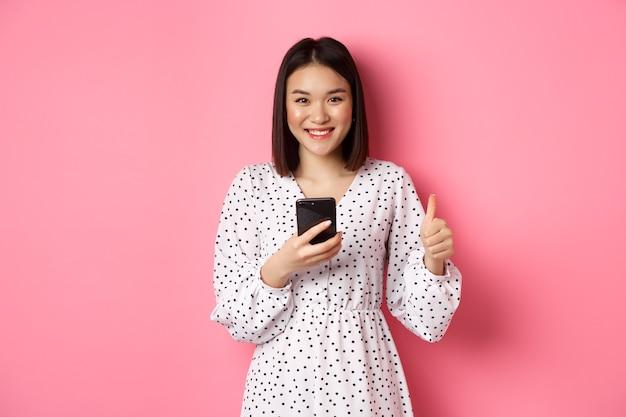 Koncepcja zakupów online i urody. zadowolona azjatycka klientka pokazując kciuk do góry, dokonując zakupu w internecie na smartfonie, stojąc na różowym tle.