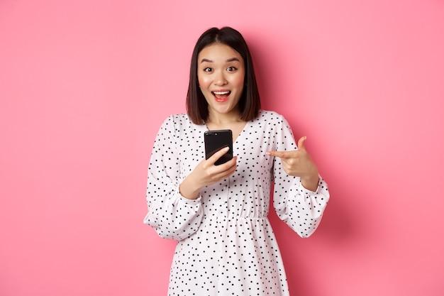 Koncepcja zakupów online i urody. zdumiona i szczęśliwa azjatka wskazująca na telefon komórkowy, rozmawiająca o internetowej ofercie promocyjnej lub aplikacji, stojąca nad różowym tłem.