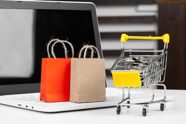 Koncepcja zakupów online, koszyk, laptop na biurku