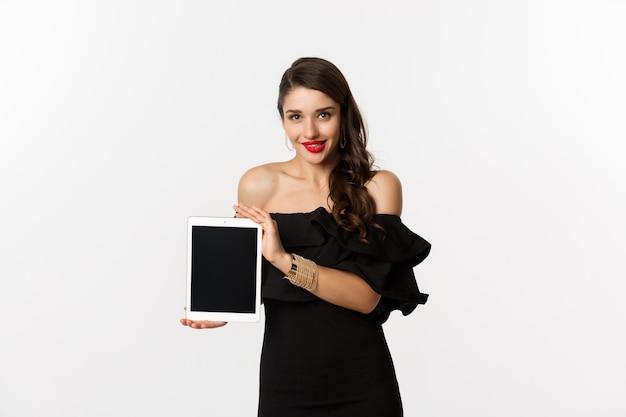 Koncepcja zakupów online. kuszona ładna kobieta w czarnej sukni, pokazując ekran cyfrowego tabletu, stojąc na białym tle. skopiuj miejsce