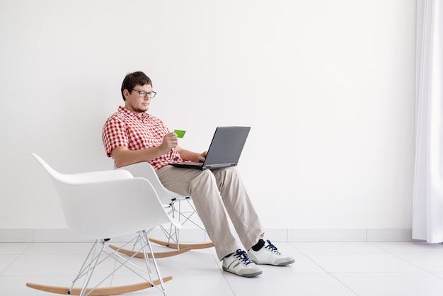 Koncepcja zakupów online. młody mężczyzna siedzi na krześle i robi zakupy online za pomocą laptopa, patrząc na kartę kredytową, kopia przestrzeń