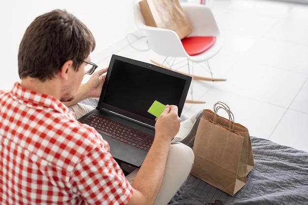 Koncepcja zakupów online. młody mężczyzna siedzi na łóżku i robi zakupy online za pomocą laptopa, patrząc na kartę kredytową, pusty ekran