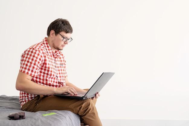 Koncepcja zakupów online. młody mężczyzna siedzi na łóżku i robi zakupy online za pomocą tabletu, kopia przestrzeń