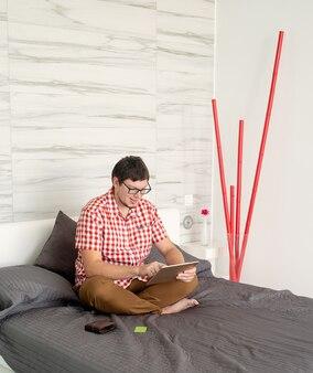 Koncepcja zakupów online. młody mężczyzna siedzi na łóżku i robi zakupy online za pomocą tabletu