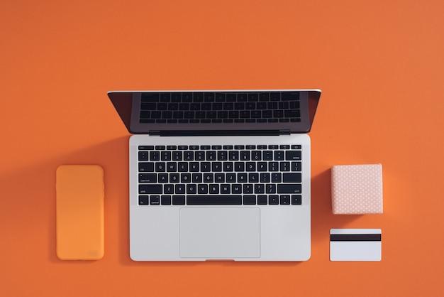 Koncepcja zakupów online na pulpicie z komputerem, stołem, torbami na zakupy, kartami kredytowymi, kuponami i produktami