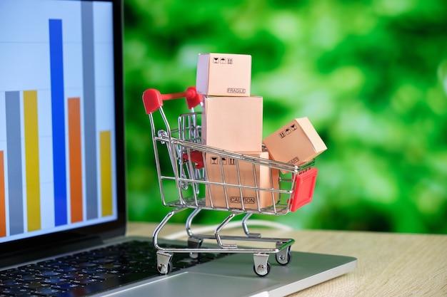 Koncepcja zakupów online. przechowuj wózek z pudełkami na laptopie.
