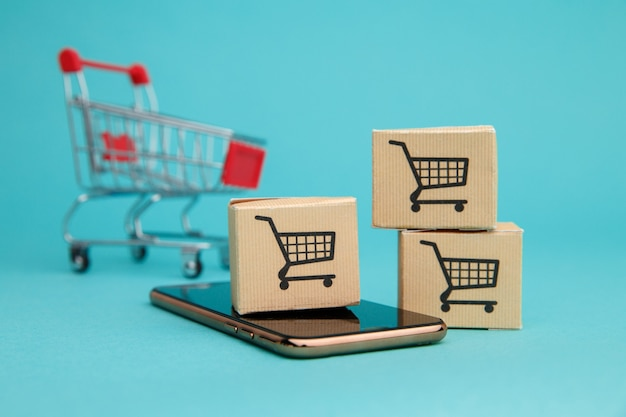 Koncepcja zakupów online. pudełka i koszyk powyżej smartfona na niebiesko.